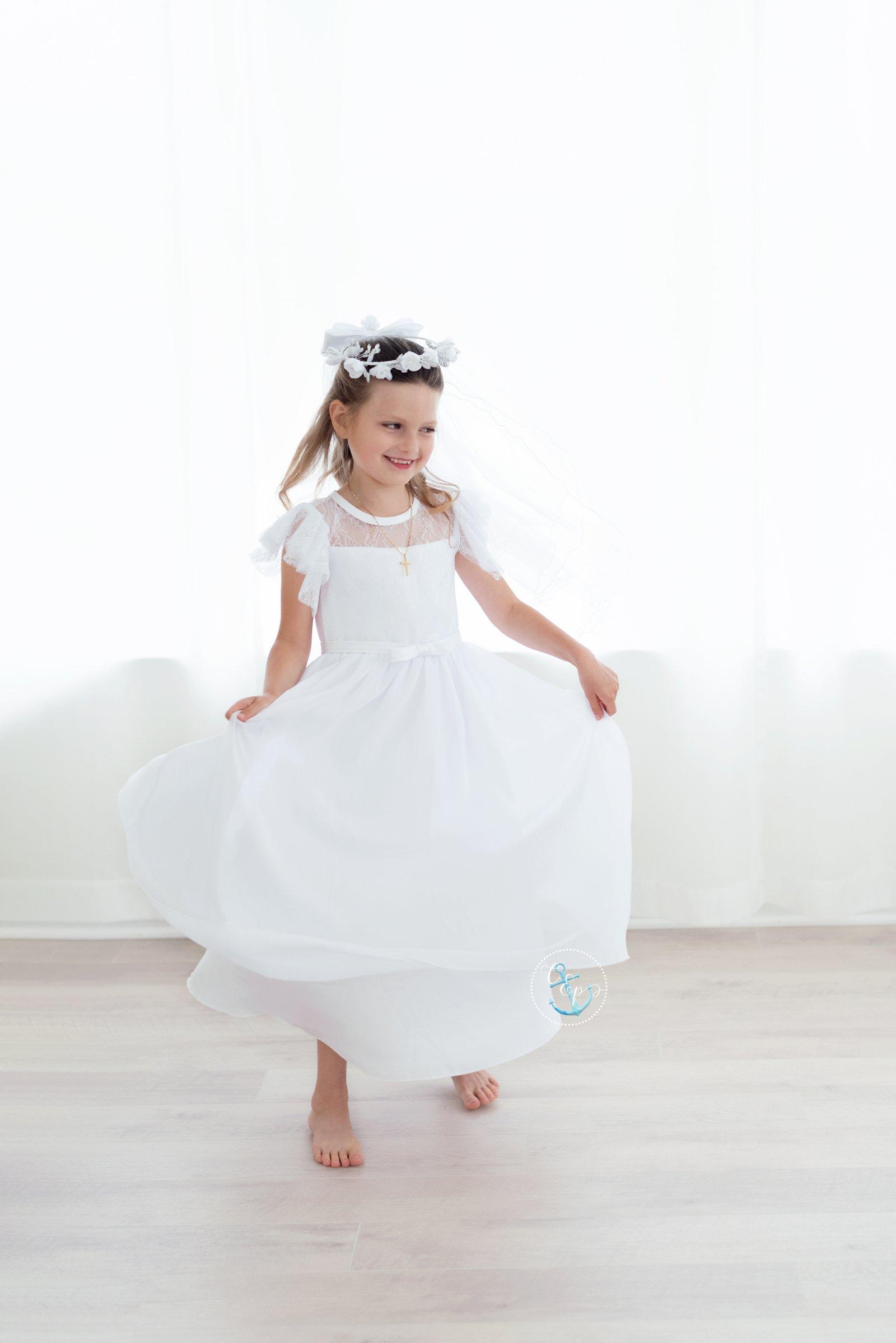First Communion girl twirling dress, White flower crown, Holy Communion portraits Maryland, Cristina Elisa Photography, white studio portraits
