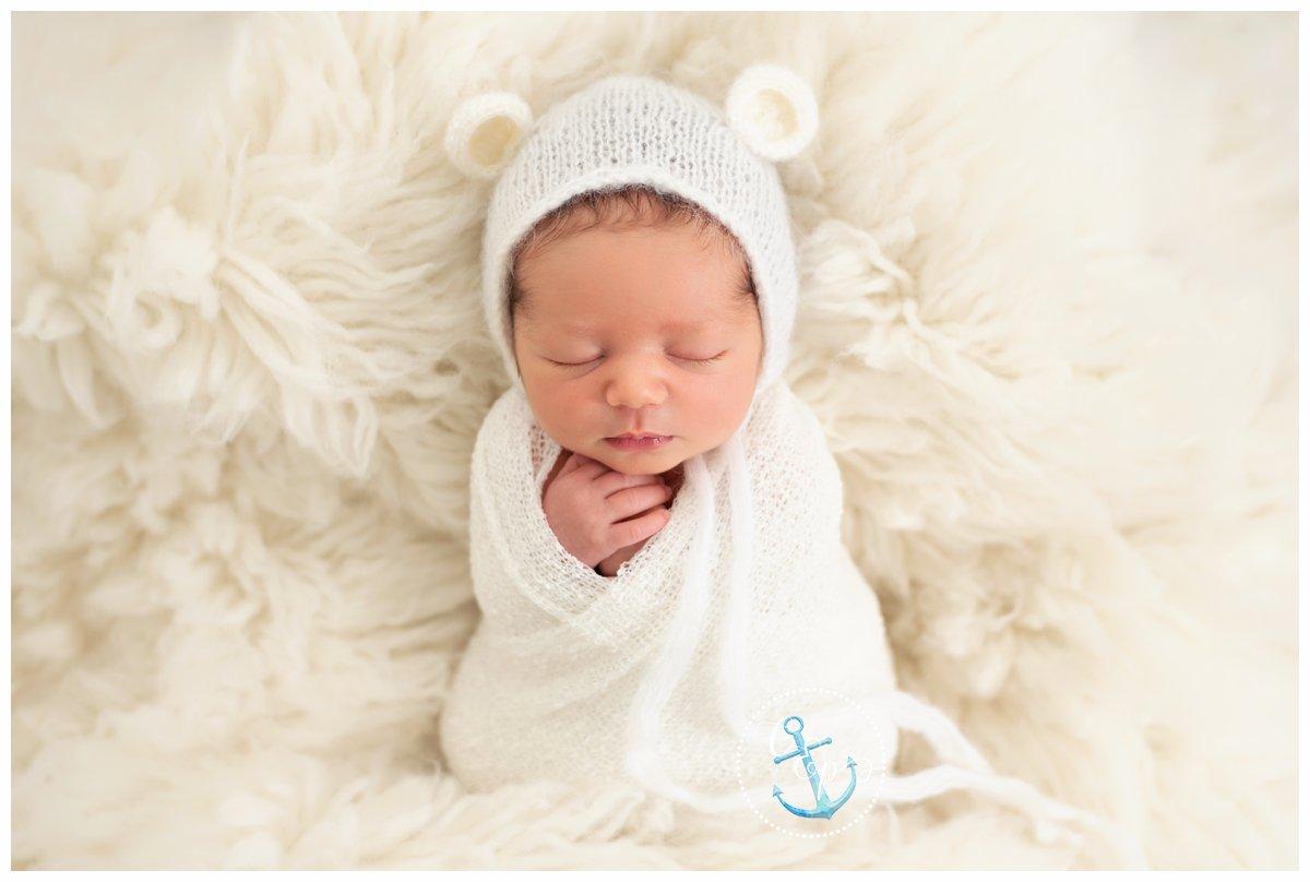 Natural light newborn portrait. Newborn swaddled in white with with teddy bear bonnet on a white flokati rug. Copyright Cristina Elisa Photography LLC Frederick Maryland Newborn Photographer