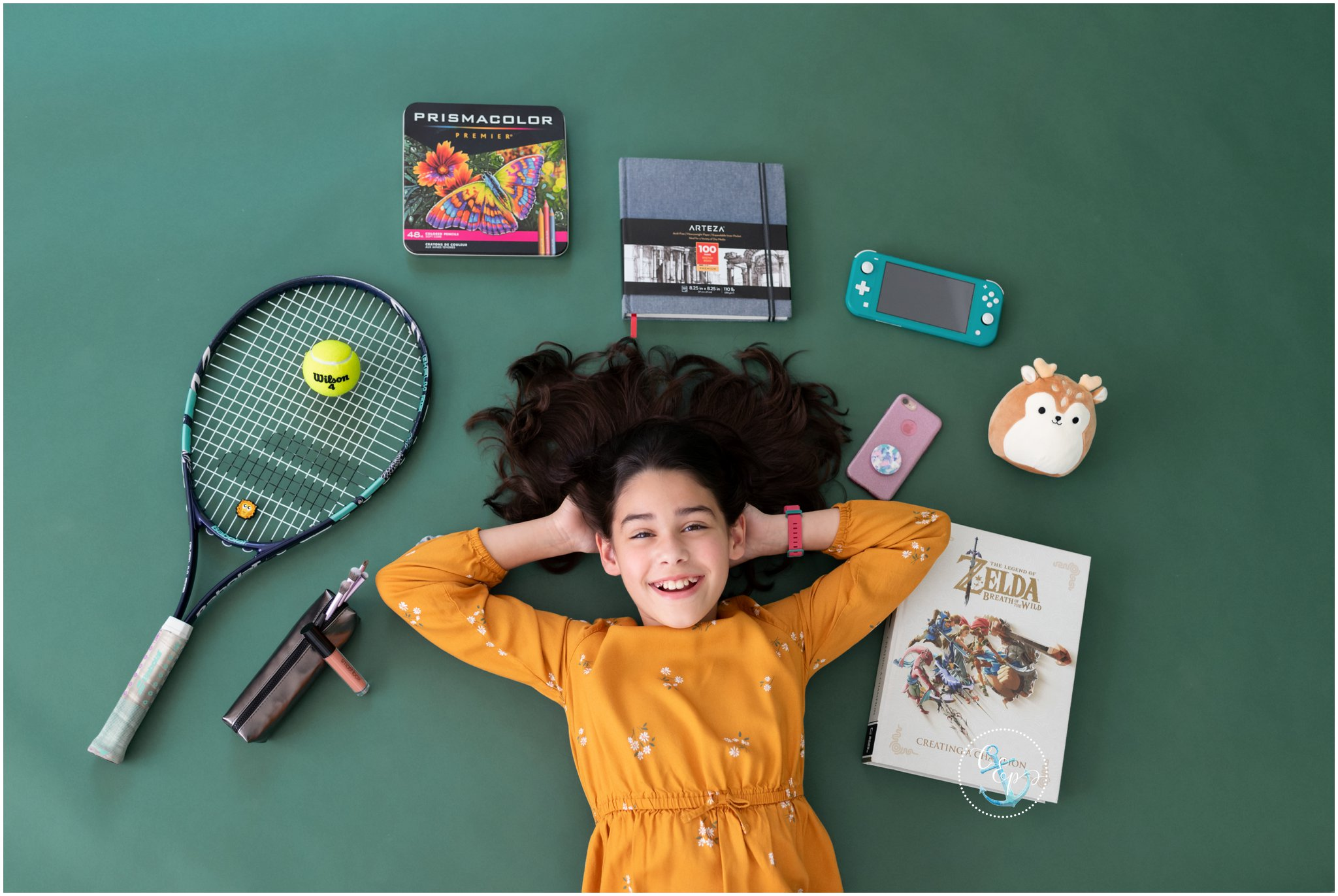 Time capsule portrait for tweens, girl surrounded by books, games, tennis racket, and art supplies, Natural light photos Frederick Maryland, Natural light child portrait photographer, Copyright Cristina Elisa Photography LLC